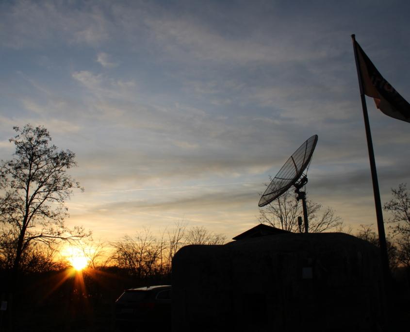 Satelitní řopík s vlajkou při západu